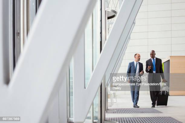Businessmen walking with luggage at airport
