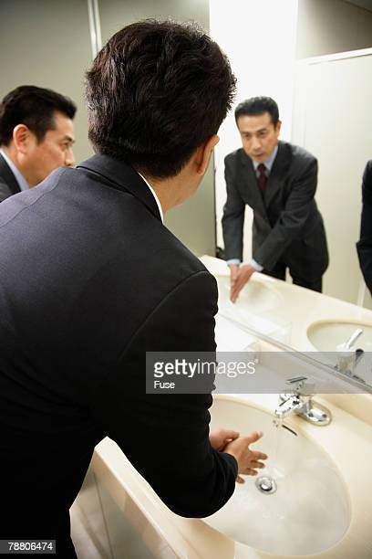 Businessmen Washing Hands in Lavatory