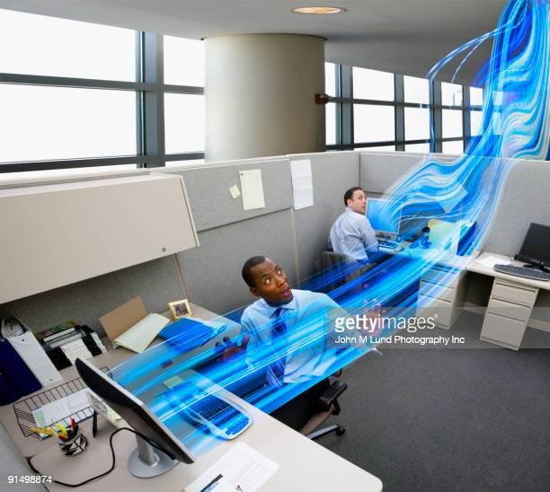 Businessmen watching light stream between computers in office