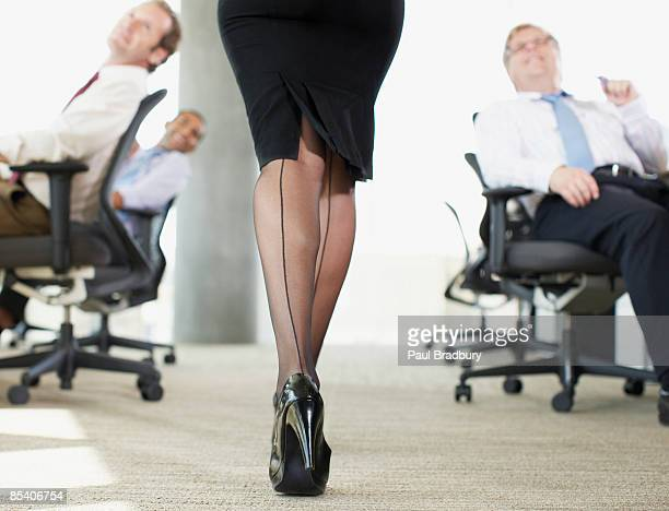 Businessmen watching sexy co-worker