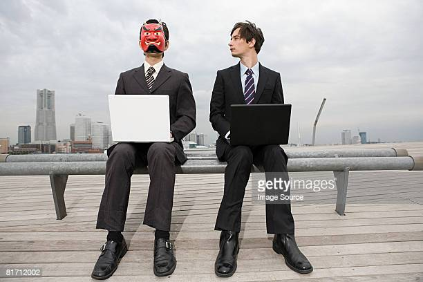 Businessmen wearing masks using laptops