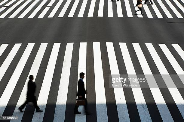 Businessmen who cross a pedestrian crossing