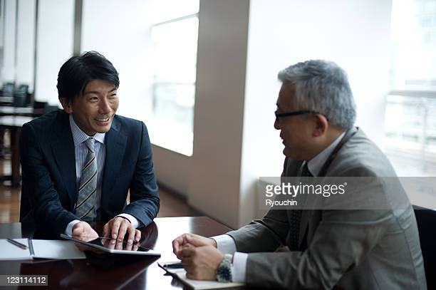 businessmen who works by using tablet in office