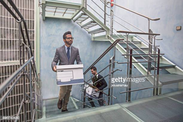 Businessmen with belongings on staircase in office