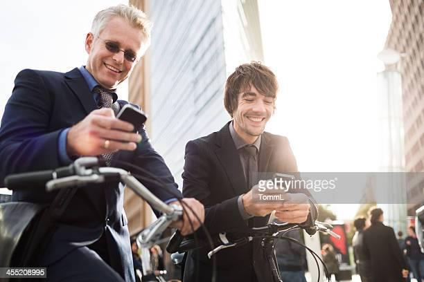 Geschäftsleute mit Fahrrad und Smartphones