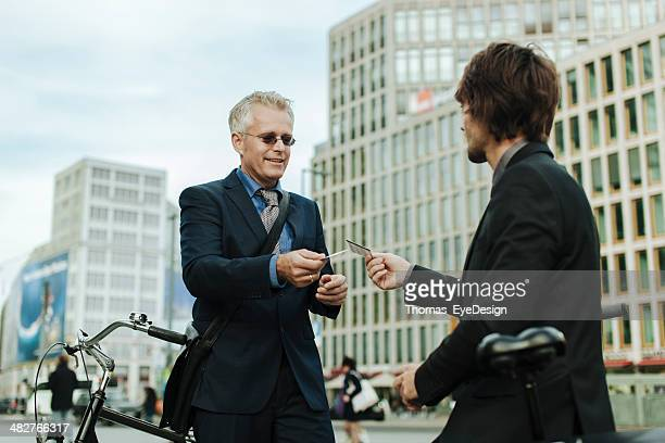 Businessmen with bicycles exchanging business cards