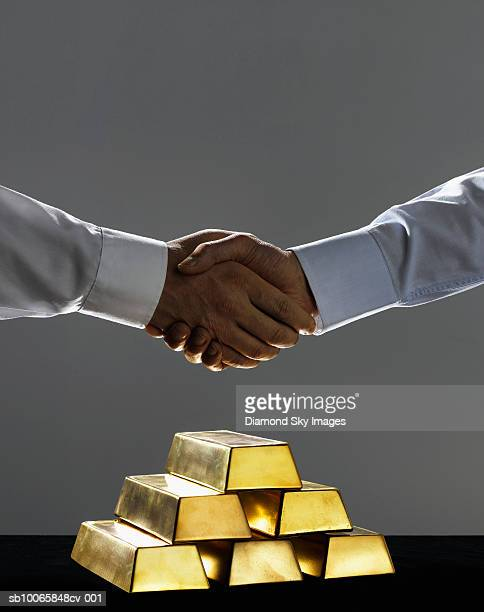 Businessmen with gold bars, shaking hands, close-up
