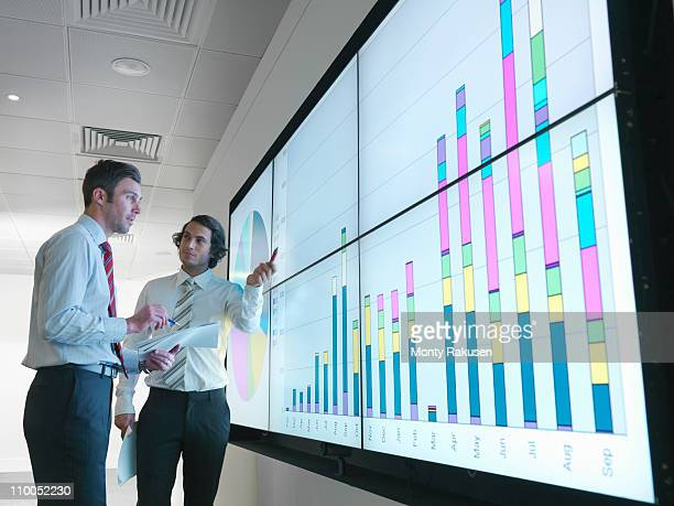 Businessmen with graphs on screen