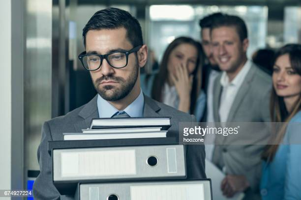 Businessmen with hands full of documents walking out of elevator while his collegues gossip behind his back