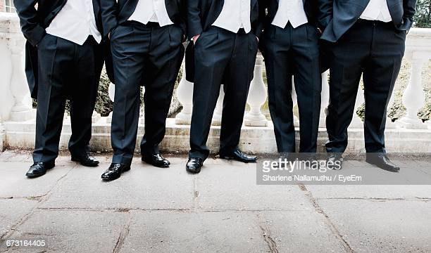 Businessmen With In Hands In Pocket In Row
