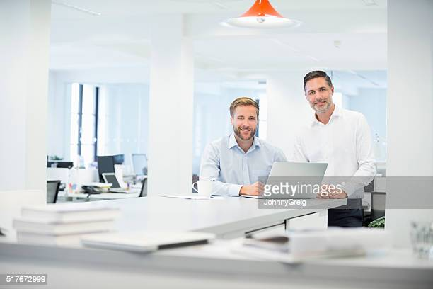 Businessmen with laptop at desk in office