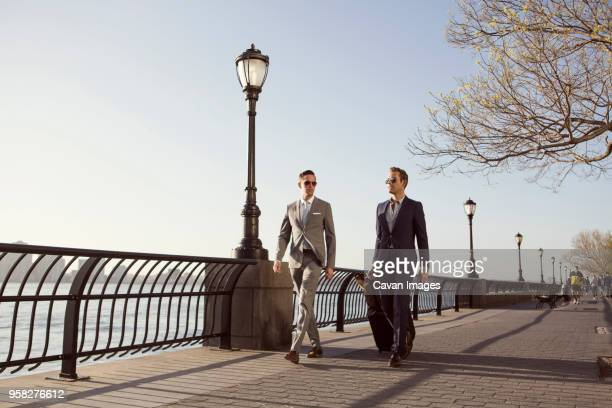businessmen with luggage walking on promenade against clear sky - gemeinsam gehen stock-fotos und bilder