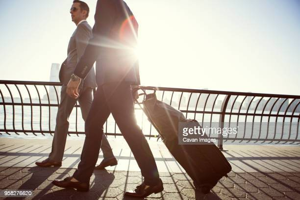 businessmen with luggage walking on promenade during sunny day - gemeinsam gehen stock-fotos und bilder