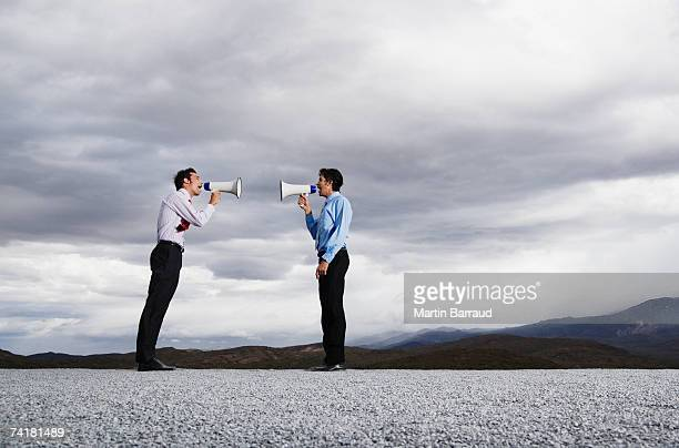 Businessmen with megaphones outdoors shouting