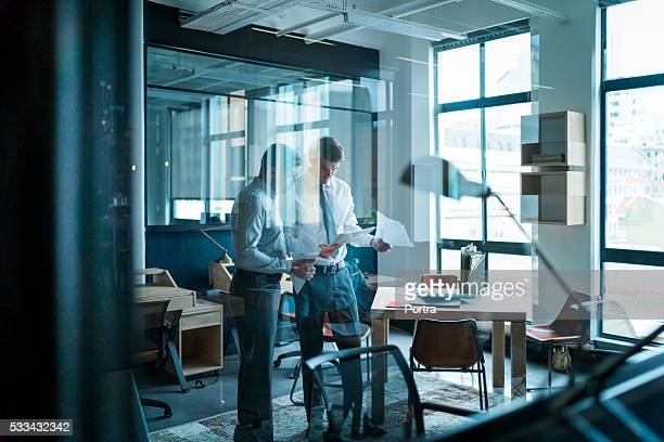 Businessmen with paperwork in glass office