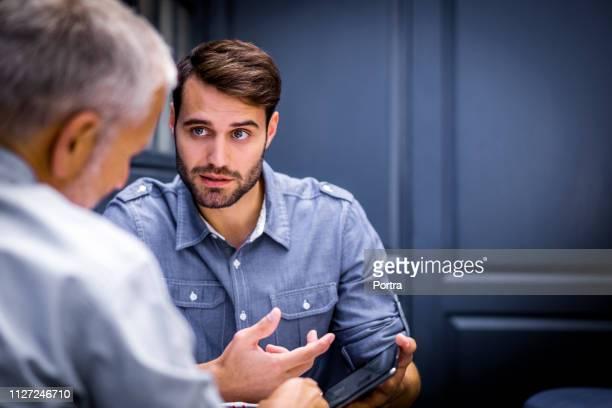 businessmen with tablet talking to colleague - camisa com botões imagens e fotografias de stock