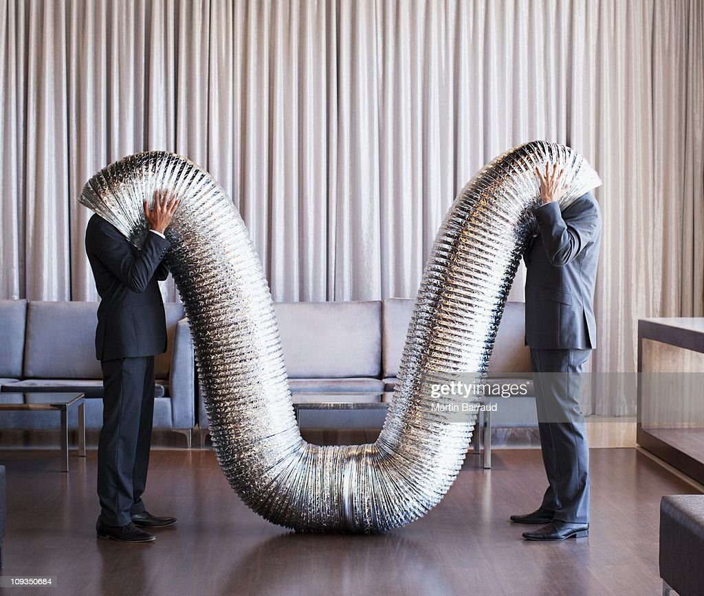 Businessmen with their heads inside metal tubing : Stock Photo