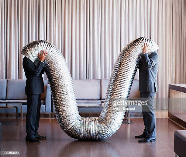 businessmen with their heads inside metal tubing - flexibility stock pictures, royalty-free photos & images
