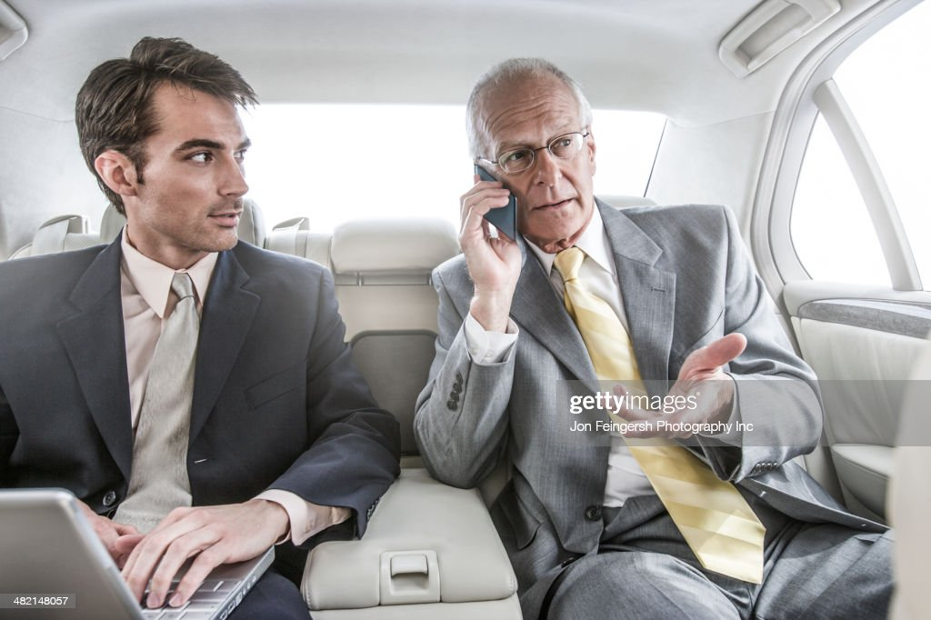 Businessmen working in backseat of car : Stock Photo