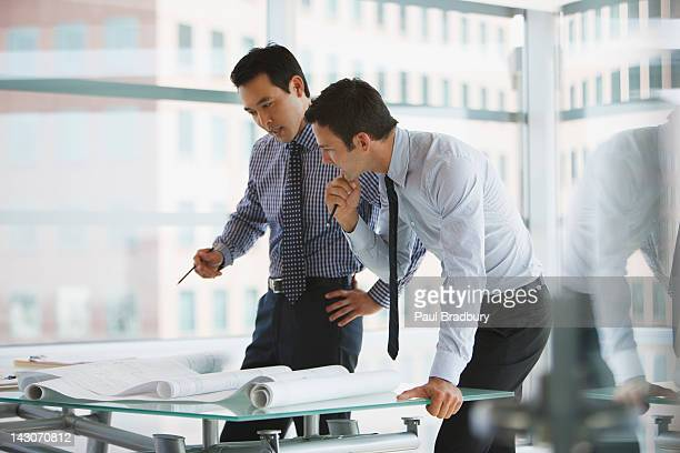 businessmen working together in office - beslissingen stockfoto's en -beelden
