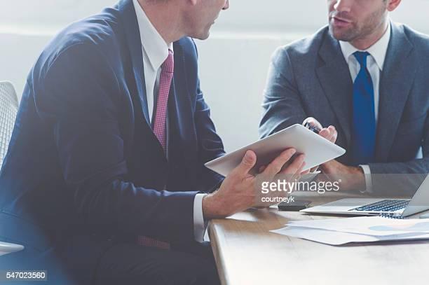 Geschäftsmänner gemeinsam auf einem Digitaltablett.