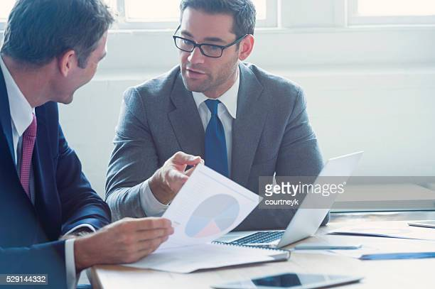 Businessmen working together on a document.