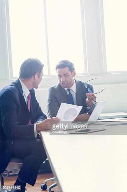 Hommes d'affaires travaillant ensemble sur un document.