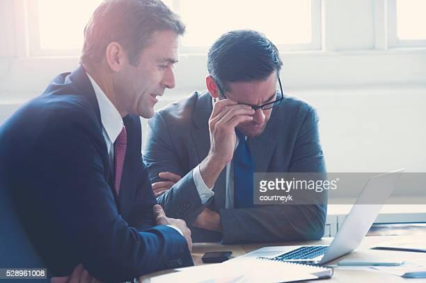 Businessmen working together on a laptop computer.