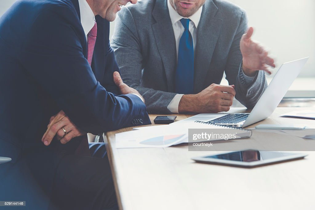 Businessmen working together on a laptop. : Stock Photo
