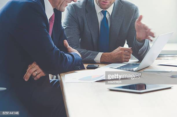 Businessmen working together on a laptop.