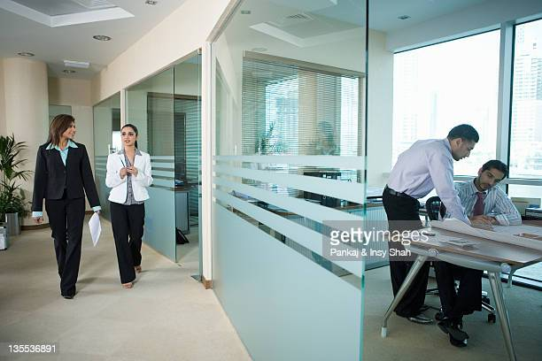 Businessmen working while businesswomen walking in office
