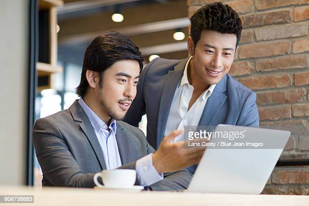 Businessmen working with laptop in caf