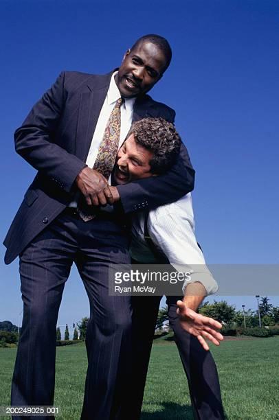 Businessmen wrestling in park