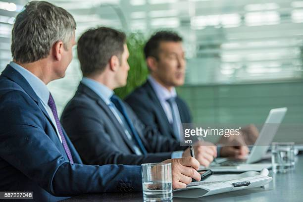 Businessmen writing notes on a meeting
