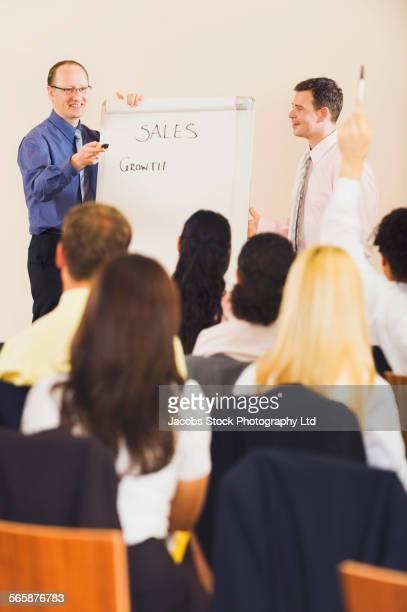 Businessmen writing on flip chart during presentation