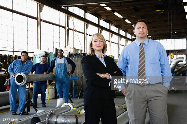 Businesspeople and Workers in a Factory