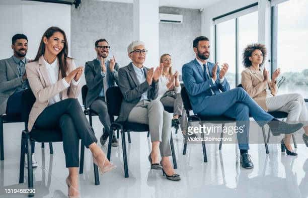 businesspeople applauding during a seminar in conference hall. - attending stock pictures, royalty-free photos & images