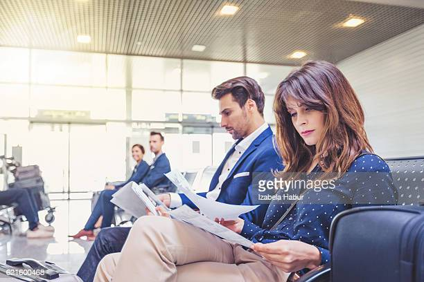 Businesspeople at airport lounge reading documents