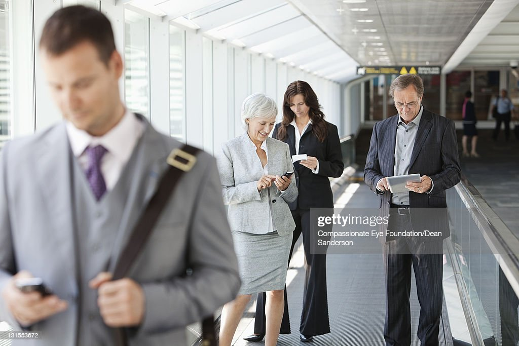 Businesspeople at airport using conveyor belt : Stock Photo
