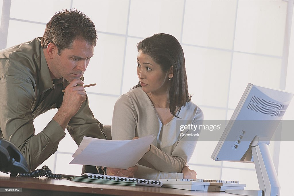 Businesspeople at desk scrutinizing report : Stock Photo