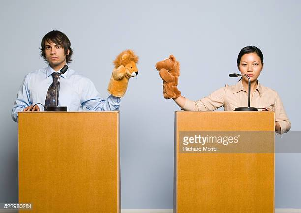 Businesspeople at Lectern Holding Puppets