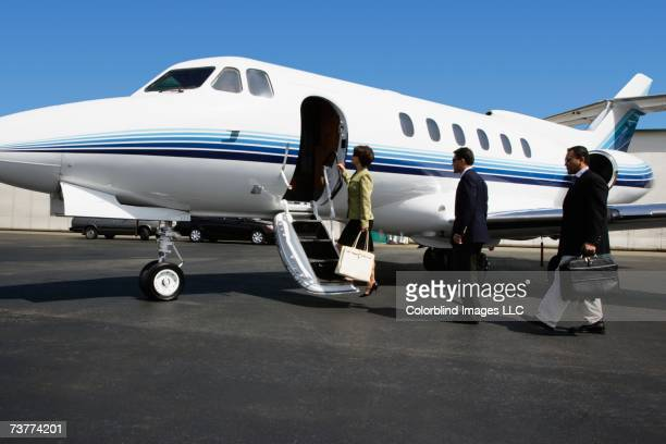 Businesspeople boarding private airplane on tarmac