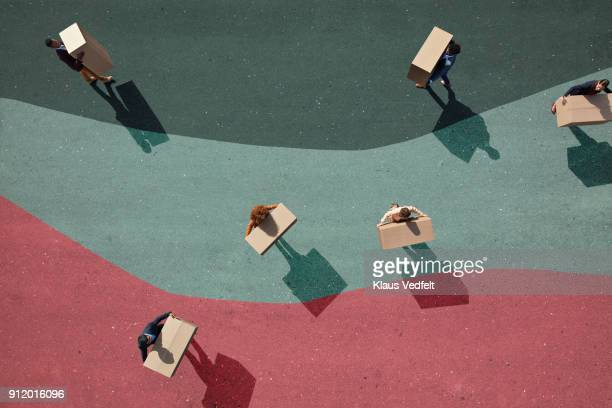 businesspeople carrying boxes around on painted lanes on asphalt - downsizing unemployment stock pictures, royalty-free photos & images