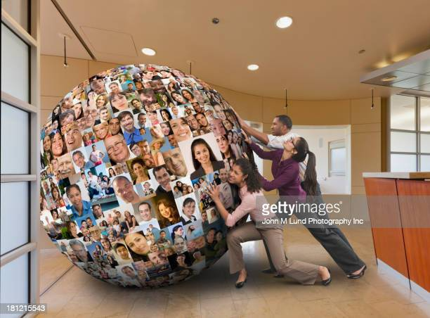 Businesspeople carrying globe on their backs
