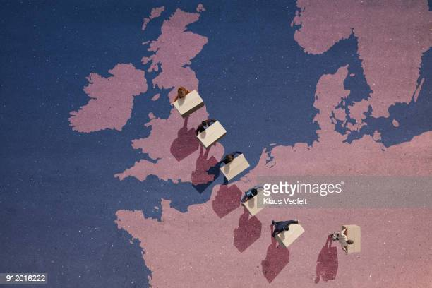 Businesspeople carrying moving boxes, while walking out of Great Britain,on painted north european map on asphalt