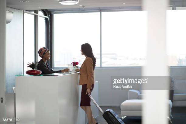 businesspeople checking in to hotel in the lobby - receptionist stock pictures, royalty-free photos & images
