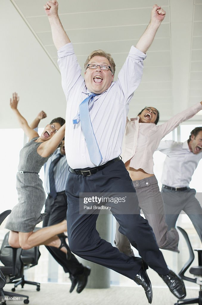 Businesspeople cheering in office : Stock Photo