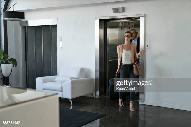 Businesspeople coming out of lift in to hotel lobby