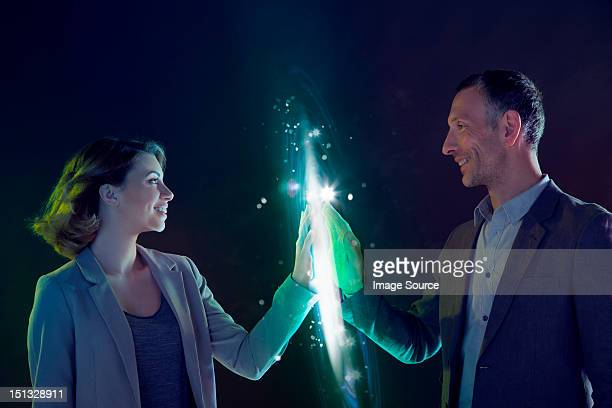Businesspeople connecting through light