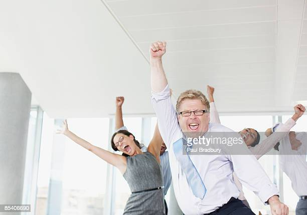 businesspeople dancing in office - cheering stock pictures, royalty-free photos & images